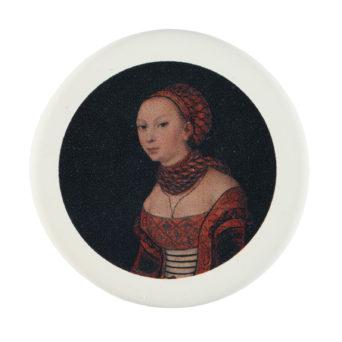 Pyöreä valkoinen pyyhekumi, johon painettu renesanssiajan vaatteisiin pukeutuneen naisen mustataustainen kuva