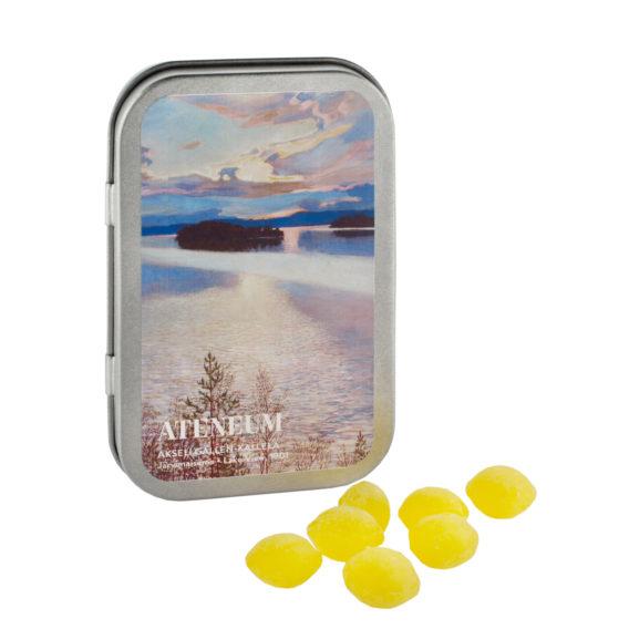 Pystyssä oleva metallirasia, jonka kannessa sinisävyinen järvimaisema, edessä keltaisia pastilleja