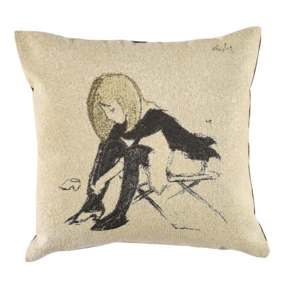 Beigenvärinen tyyny, jossa istuva tyttö solmii kengännauhojaan
