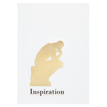 Valkoinen vihko jonka jonka alareunassa on ajattelija-patsaan kultainen siluetti, sen alapuolella teksti Inspiration mustalla fontilla