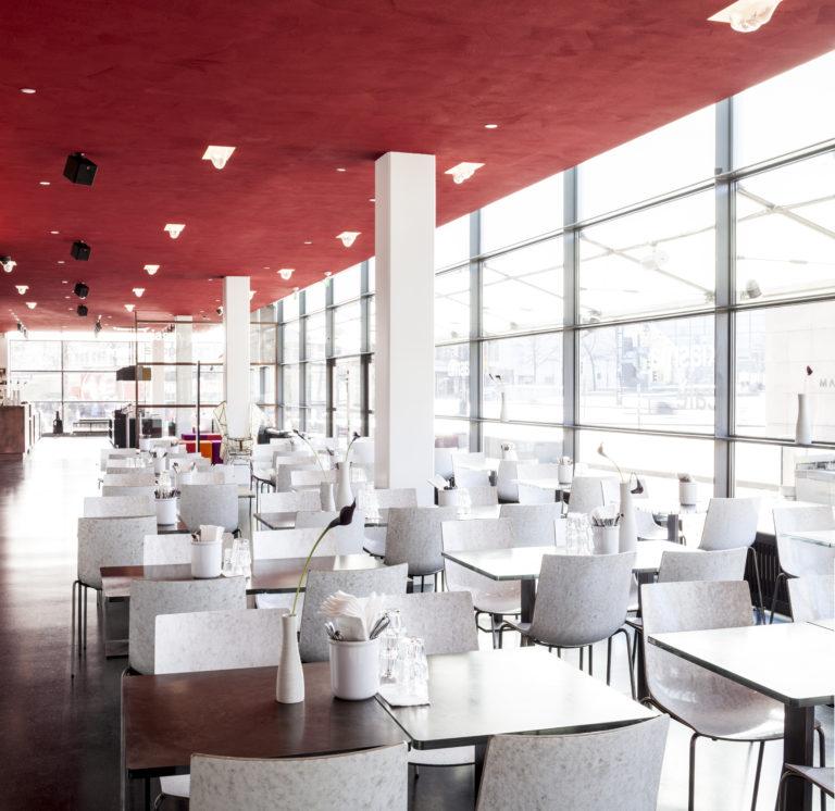 Kiasma Cafén valkoiset tuolirivistöt ja niiden pöydät, punainen katto ja suuret lasi-ikkunat kuvattuna kahvilan perältä.