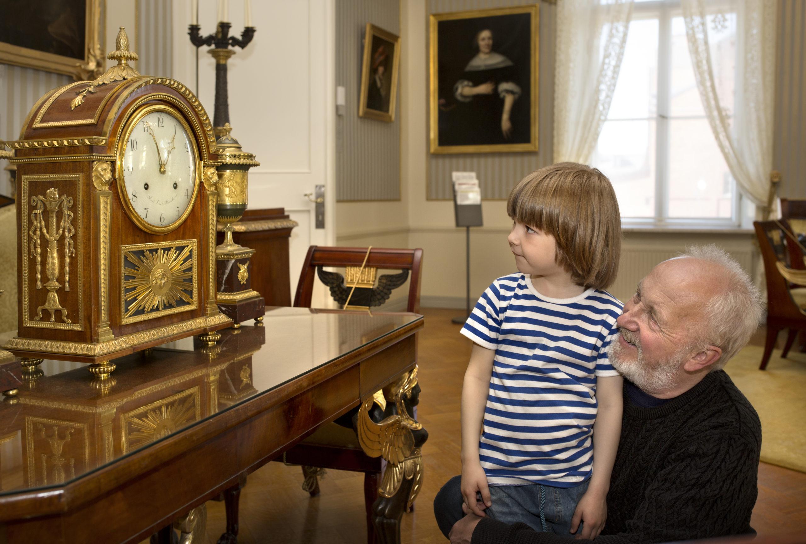 isoisä ja lapsi katselevat museoesineitä