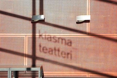 Kiasma teatterin logon varjo auringonvalossa kuvattuna seinää vasten.
