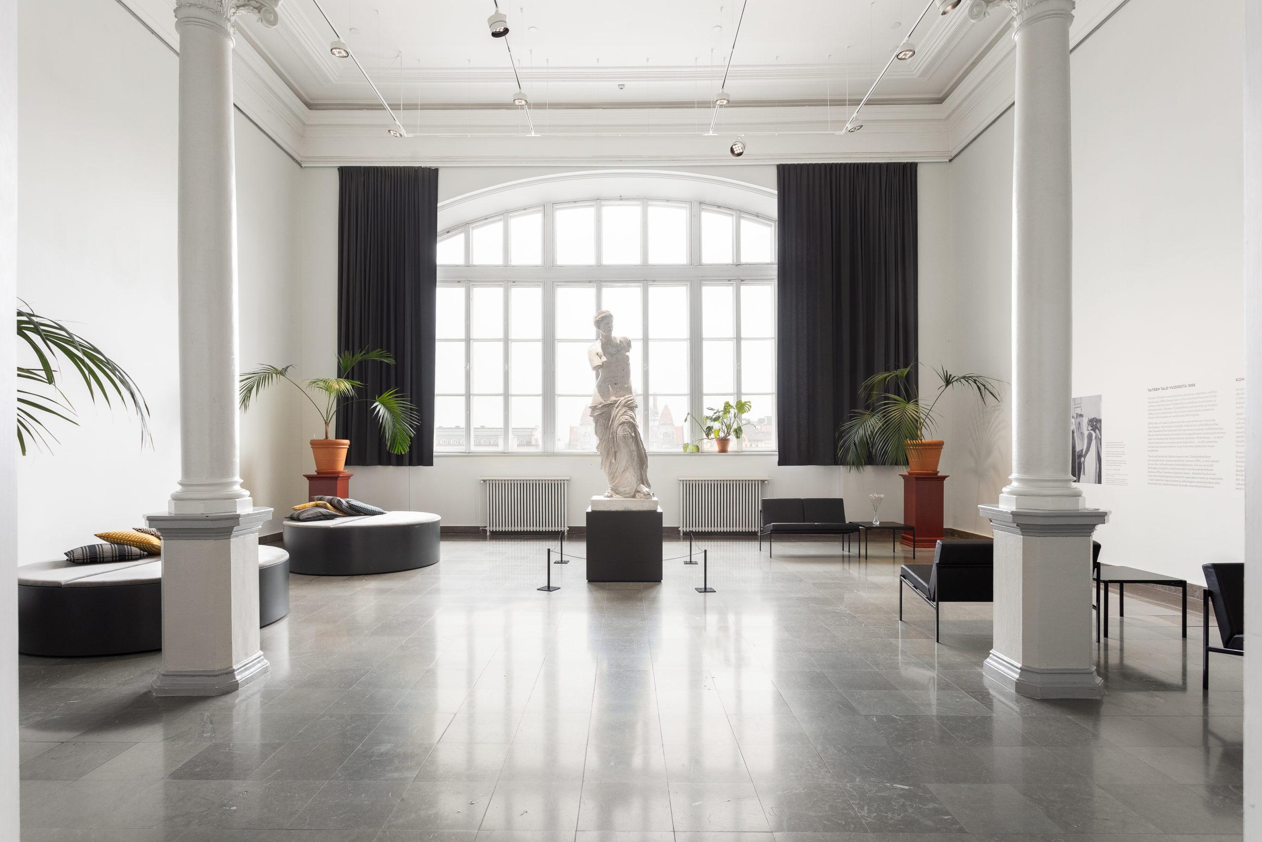 Ateneumin Cubus-sali kuvattuna ovelta, iso koko seinän ikkuna taustalla jonka edessä Milon Venus -patsas.