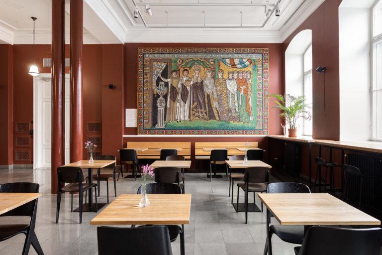 Ateneum Bistro, takaseinällä mosaiikki ja etualalla huonekaluja.