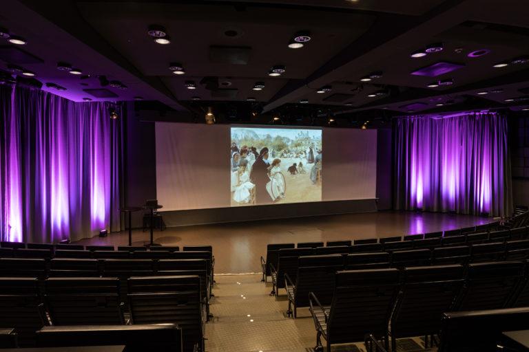 Ateneum-sali presentaation hetkellä, violetti sivuverhovalo ja taidekuva kankaalla.