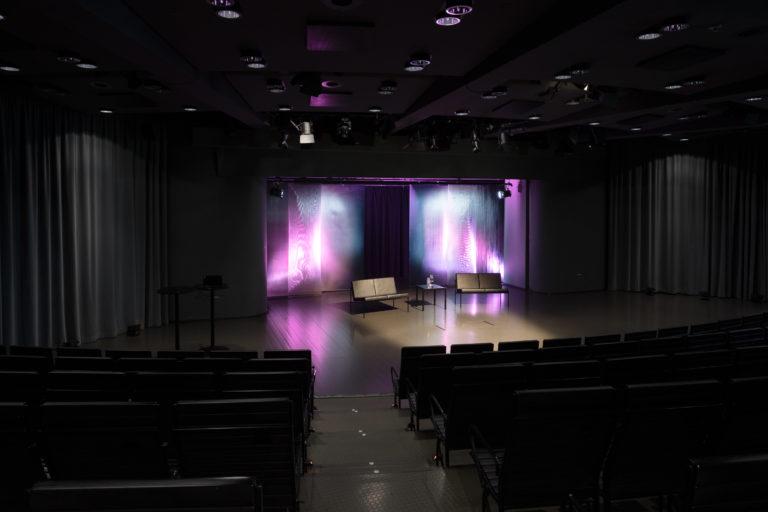 Ateneum-salissa paneelikeskustelu, violetti valaistus.