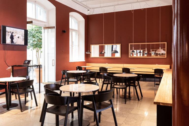 Ateneum Bistro kokouskäytössä, screenillä taidekuva ja etualalla huonekaluja.