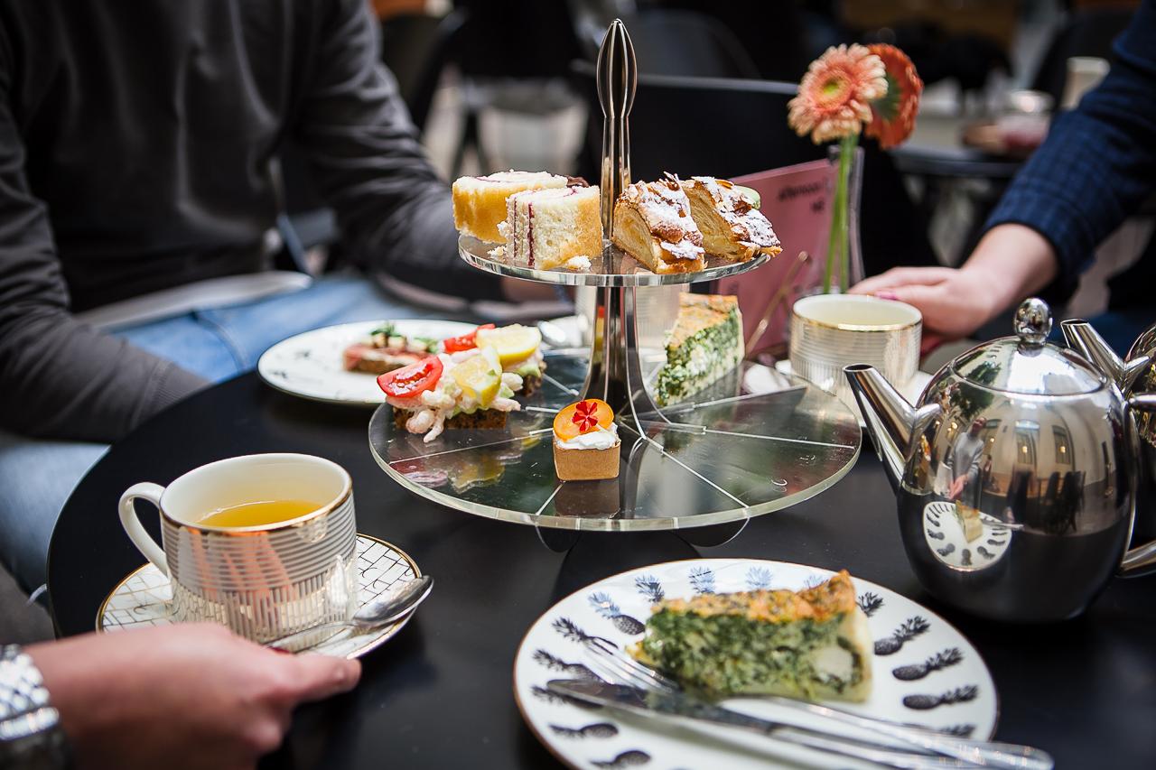 Ateneumin Bistron tarjoiluja, teetä valkoisissa kupeissa ja kaksikerroksinen tarjoilulautanen, jossa herkkuja. Pyöreälle pöydälle katettuna, ruokailijoista näkyvät vain kädet.