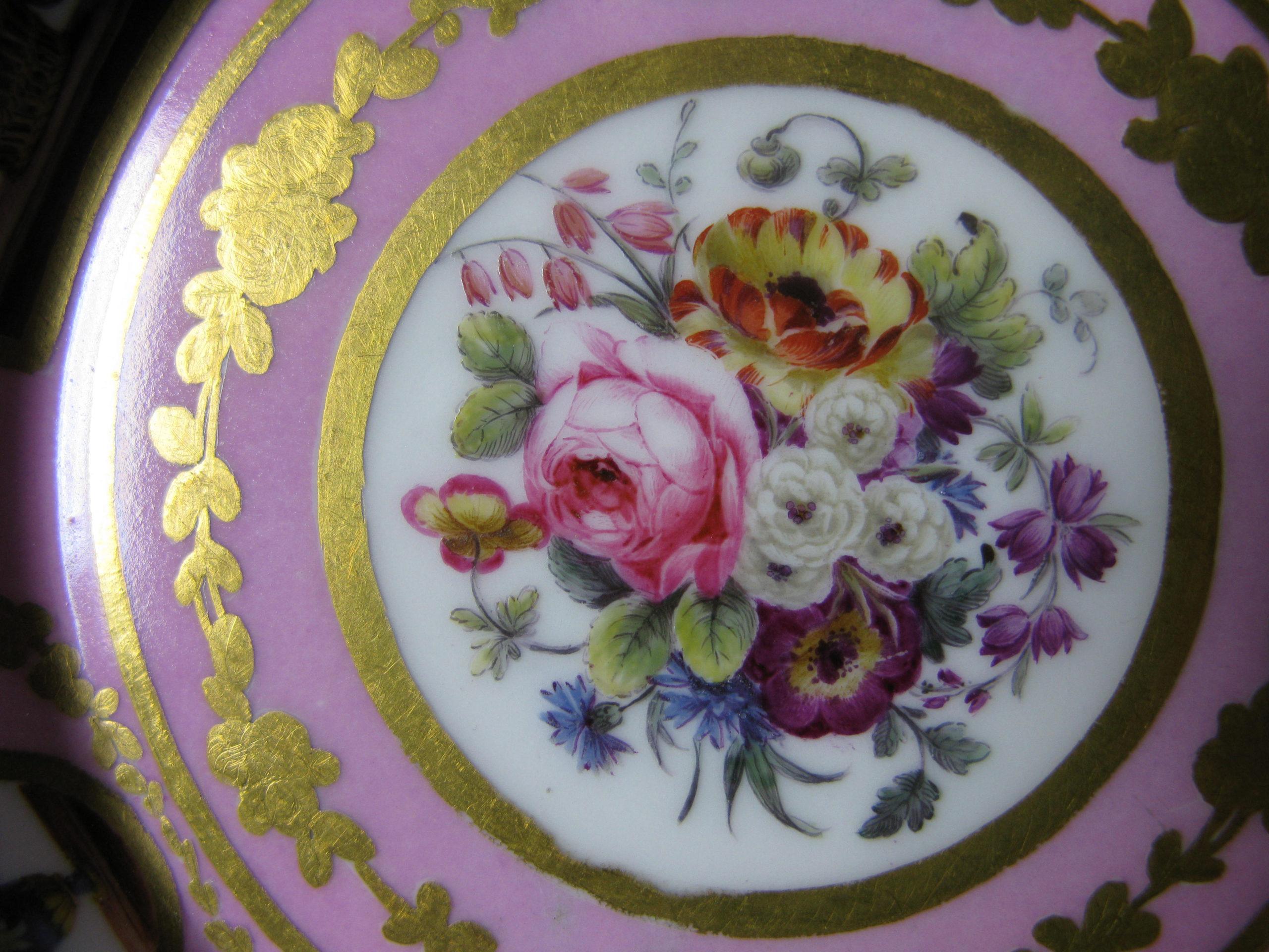 Yksityiskohta astian posliinimaalauksesta, jossa kullatulla reunuksella pyöreä kukka-asetelma ja vaalean liila tausta.
