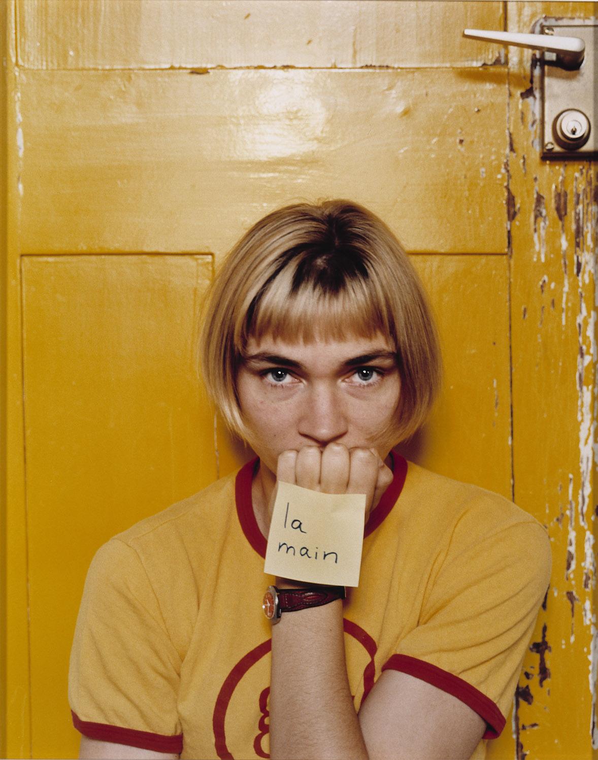 Vaaleapolkkatukkainen nainen kuvattuna edestäpäin keltaisessa t-paidassa keltaista taustaa vasten keltainen lappunen nyrkkiinsä kiinnitettynä.