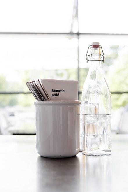 asetelma pöydällä, vesipullo ja servettitelinne, serveteissä teksti kiasma café. Taustalla ikkuna.