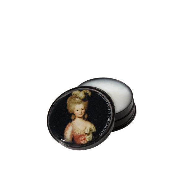 Pyöreä huulirasvarasia, jonka kannessa naisen muotokuva