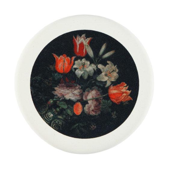 Pyöreä pyyhekumi, jossa kukkia tummalla taustalla