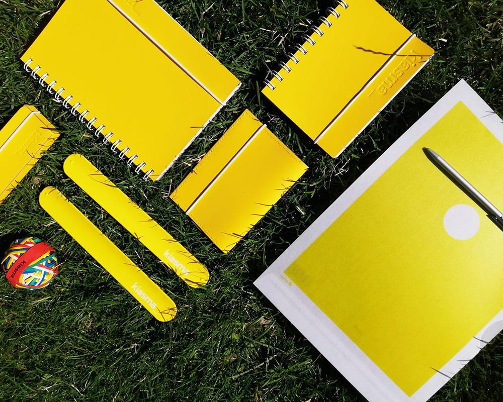 Keltaisia muistikirjoja ja toimistotarvikkeita nurmikolla