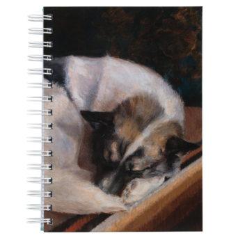 Kierremuistikirja, jonka kannessa vaalea koira makaa matolla