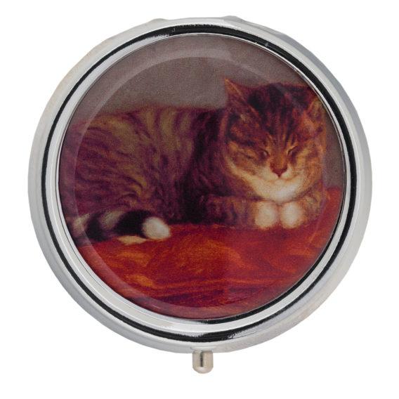 Pyöreä rasia, jossa punaisella tyynyllä majaava kissa