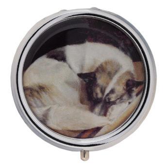 Pyöreä rasia, jonkan kannessa vaalea makaava koira