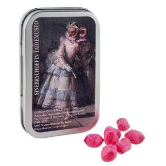 Vaaleanpunaisia pastilleja ja metallinen pastillirasia, jonka kannessa yksityiskohta Pulcinellan riemusaatto -teoksesta