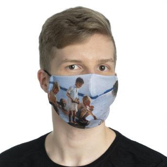 Vaalean pojan kasvoilla kankainen maski jossa taideteoksen kuva