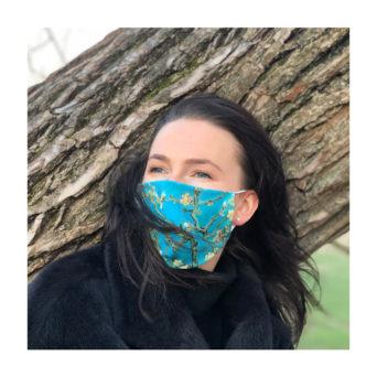 Nainen jolla turkoosisävyinen taidekuvalla varustettu kangasmaski kasvoillaan