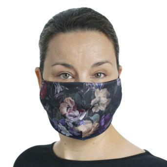 Naisen kasvoilla kankainen maski, jossa tummalla pohjalla kukkia