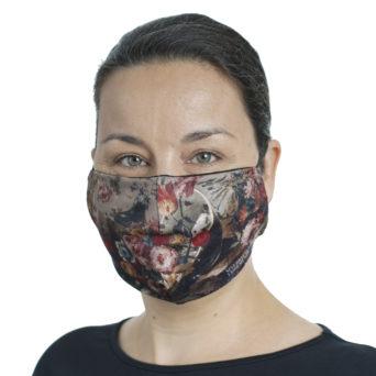 Naisen kasvoilla kankainen maski, jossa vaaleanruskealla pohjalla kukkia