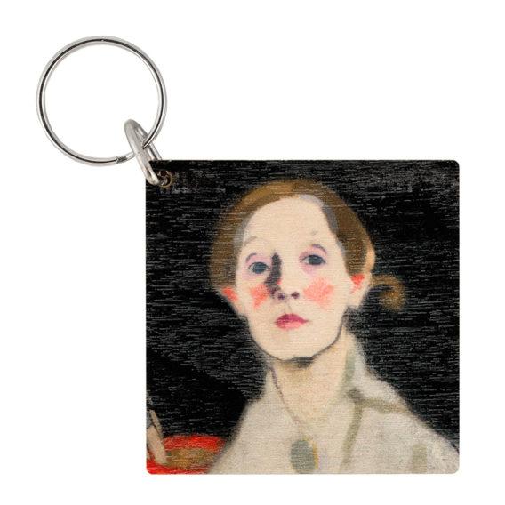 Neliönmallinen puinen avaimenperä jossa naisen kasvokuva mustalla taustalla