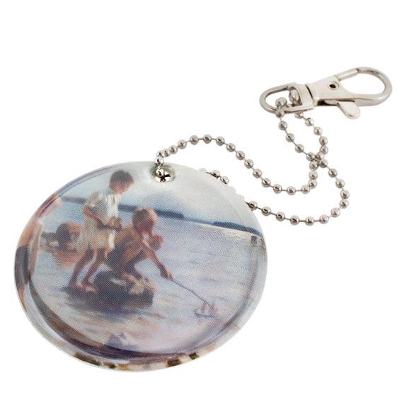 Pyöreässä heijastimessa rannalla leikkiviä poikia