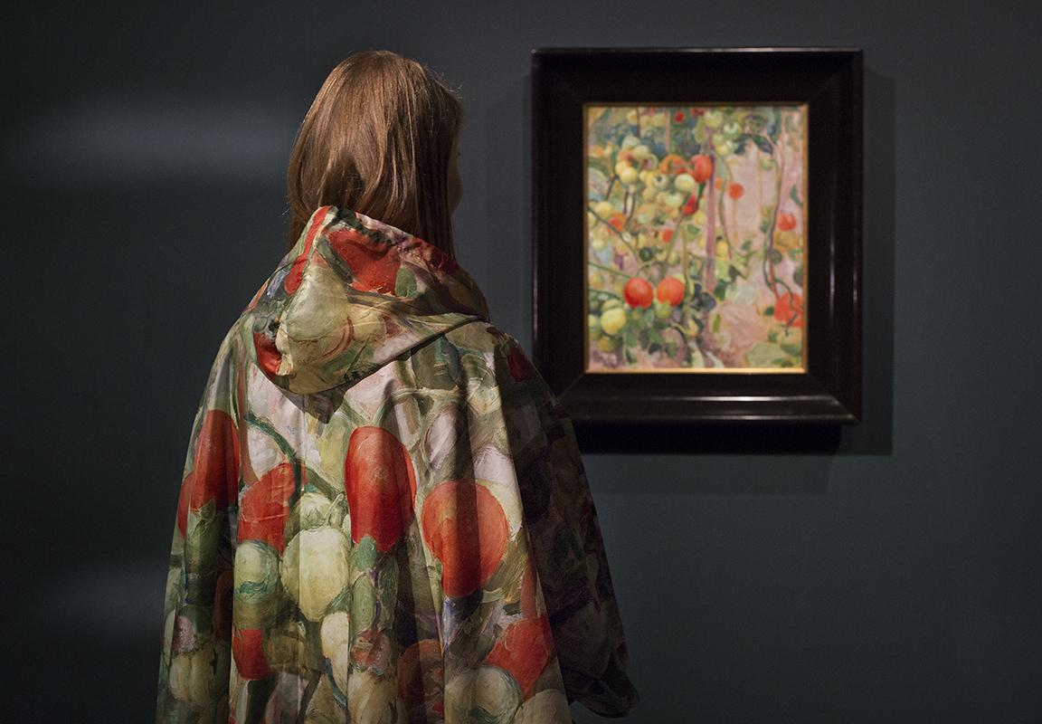 Tomaattikuvioiseen sadeviittaan pukeutunut nainen katsoo museossa Tomaatteja-maalausta